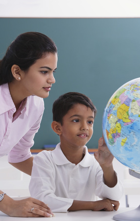 librarians: teacher and student look at globe LANG_EVOIMAGES