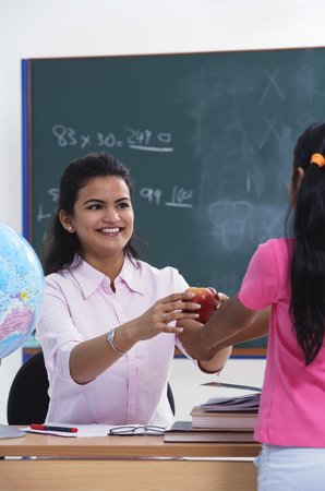 librarians: student handing apple to teacher