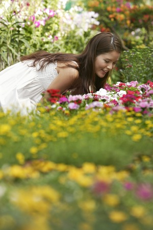 Young woman leaning over to smell the flowers