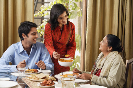 and the horizontal man: woman serves dinner to man and older woman (horizontal) LANG_EVOIMAGES
