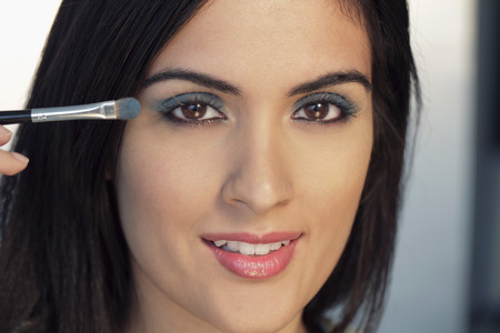 indian subcontinent ethnicity: Head shot of young woman putting on make up