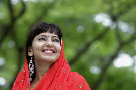 indian subcontinent ethnicity: Head shot of Indian woman smiling with red sari over her head