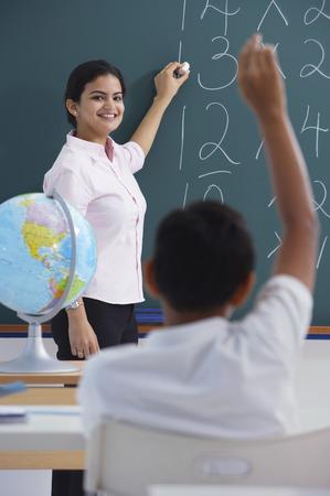 librarians: teacher at chalkboard, boy raises hand