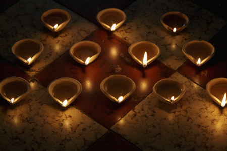 A group of lit clay oil lamps on floor