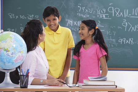 librarians: teacher speaking to two students, students smiling LANG_EVOIMAGES