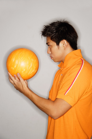 side view: Man looking at bowling ball, side view LANG_EVOIMAGES