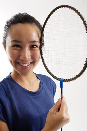 vietnamese ethnicity: Woman holding badminton racket next to her face, smiling
