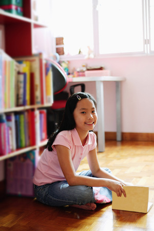 Girl sitting cross-legged on floor, holding book, looking at camera Stock Photo