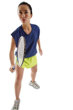 vietnamese ethnicity: Woman holding badminton racket, looking upwards