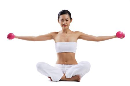 Woman sitting on floor, legs crossed, lifting dumbbells