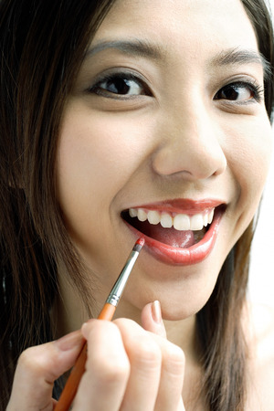 Woman smiling at camera, putting on lipstick with lip brush