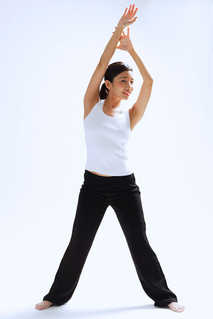 Woman standing, hands raised over her head, legs apart Stock Photo
