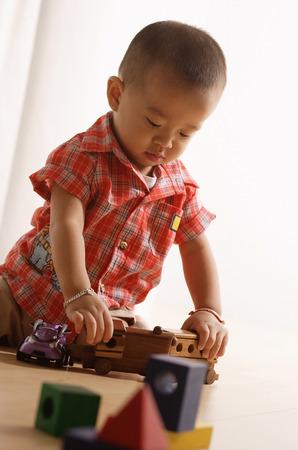 arrodillarse: niño jugando con el tren de juguete