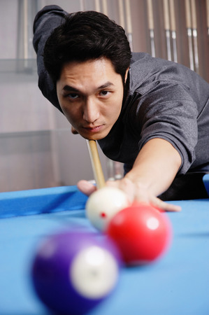 Man holding pool cue, aiming at ball