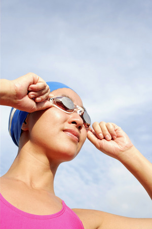 vietnamese ethnicity: Woman adjusting swimming goggles, looking away
