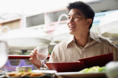 Man in cafe, menu in front of him, holding glass of water, looking away