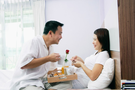 Couple in bedroom, breakfast tray between them
