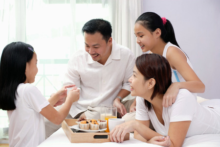 Family of four in bedroom, breakfast tray on the bed next to them Stock Photo - 69308486