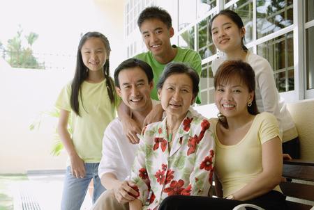 three generation: Three generation family on patio, looking at camera, smiling