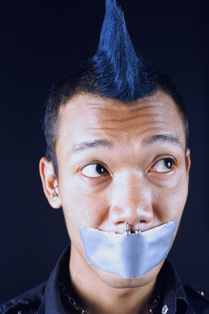Man with mohawk, mouth taped shut, looking away