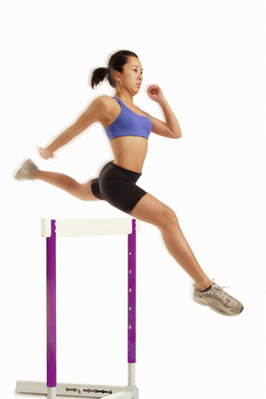 vietnamese ethnicity: Woman jumping over hurdle LANG_EVOIMAGES