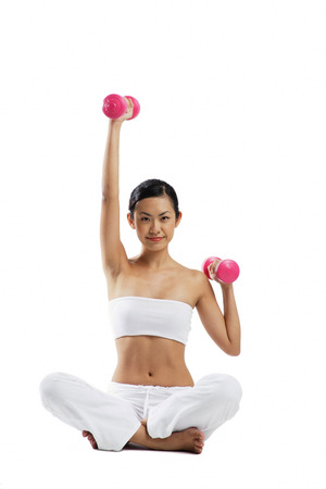 Woman sitting crossed legged on floor, lifting dumbbells, looking at camera