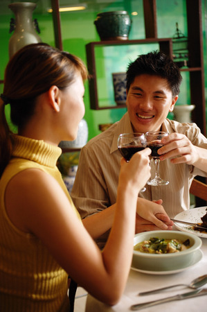 Couple dining in Chinese restaurant, toasting with wine glasses Banco de Imagens