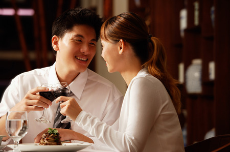 looking for love: Couple in restaurant, sitting side by side, toasting with wine glasses LANG_EVOIMAGES
