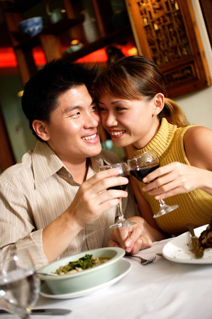 looking for love: Couple in restaurant, sitting cheek to cheek, holding wine glasses