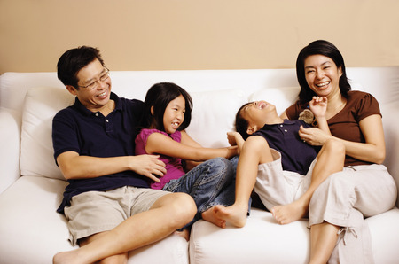 Family of four on sofa, sister tickling brother Stockfoto
