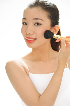 Woman applying blusher with make-up brush