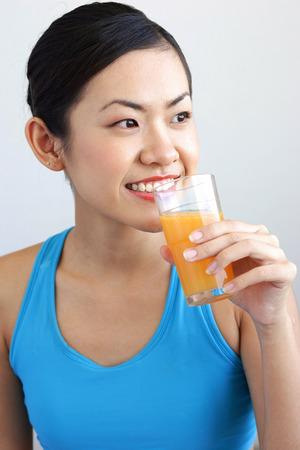 verre de jus d orange: Woman holding glass orange juice to mouth, looking away LANG_EVOIMAGES