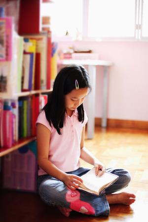 crosslegged: Girl sitting cross-legged in bedroom, reading book