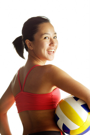vietnamese ethnicity: Woman carrying basketball, looking over shoulder at camera