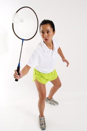 vietnamese ethnicity: Woman hitting shuttlecock with badminton racket