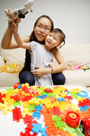 3 4 years: Mother and daughter playing toy airplane