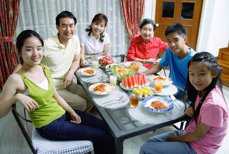 three generation: Three generation family around dining table, smiling at camera