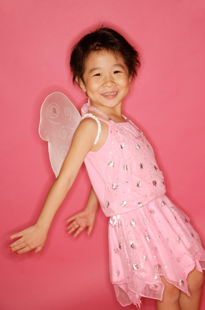 Young girl in pink dress with artificial wings, smiling at camera, hands stretched behind her