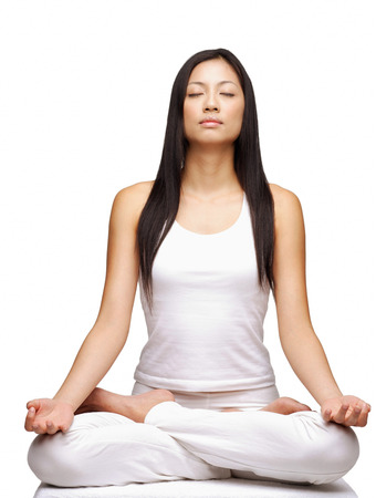 Woman practicing yoga, sitting in lotus position, eyes closed