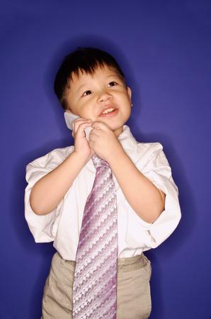 Boy wearing oversized tie, using mobile phone
