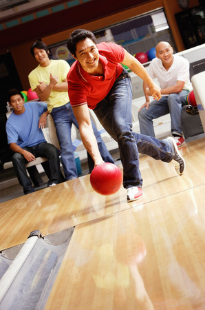 Man bowling, friends cheering in the background