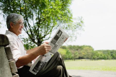 Senior hombre sentado en el banco en el parque leyendo el periódico Foto de archivo - 69309901