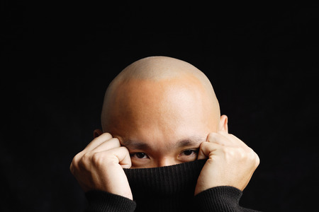 obscured: Man hiding behind turtleneck, obscured face
