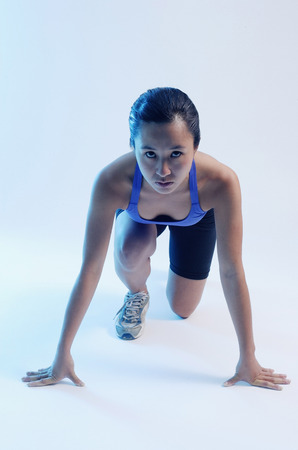 mujer arrodillada: Woman kneeling at starting position, looking at camera