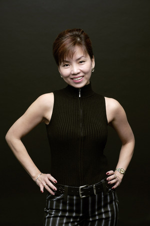 Woman standing, hands on hips, smiling at camera