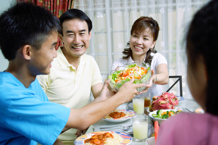 Mother passing food to family members Stock Photo