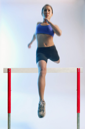 vietnamese ethnicity: Woman running and jumping over hurdle