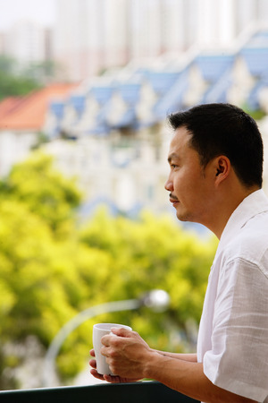 Man leaning on railing, looking away, holding mug Stock Photo