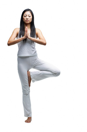 Woman standing in yoga position, eyes closed