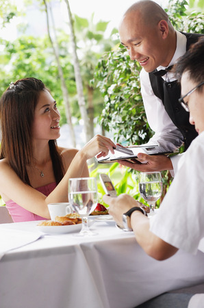 over paying: Couple in restaurant, woman making payment to waiter LANG_EVOIMAGES
